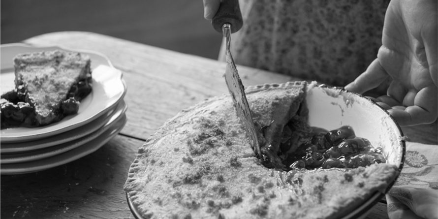black and white photo of lady cutting pie
